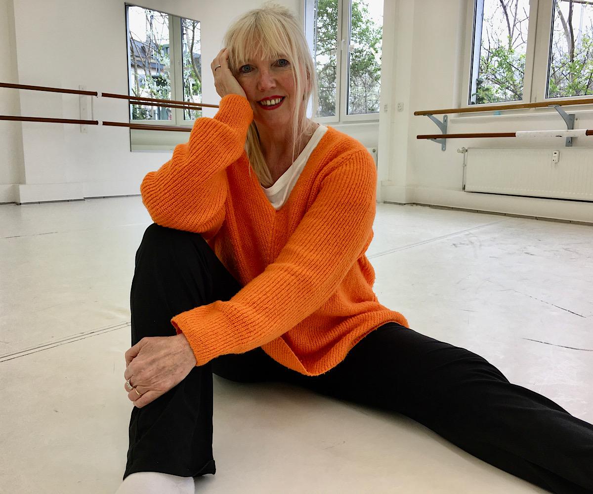 Isolde sitzt am Boden eines Ballettsaal und schaut ganz entspannt in die Kamera
